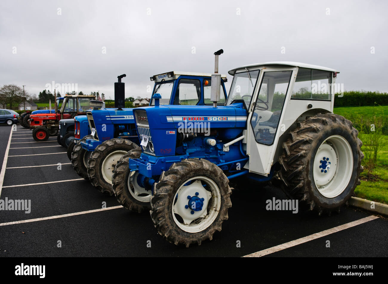 two blue ford farm tractors parked in a carpark other vintage stock