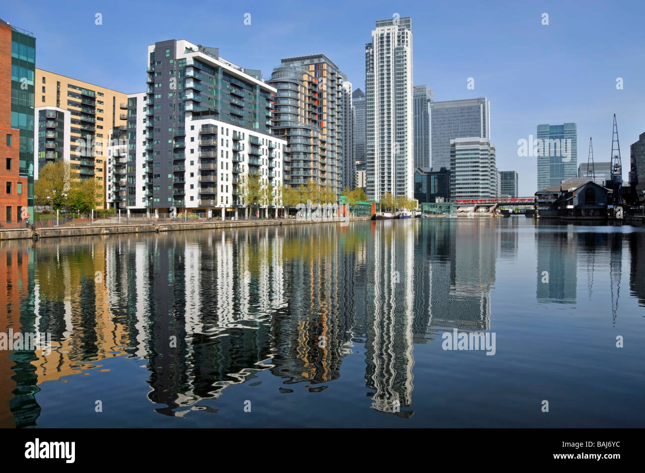 Waterside high rise apartment developments beside Millwall Docks close to Canary Wharf with Citi bank tower block - Stock Image