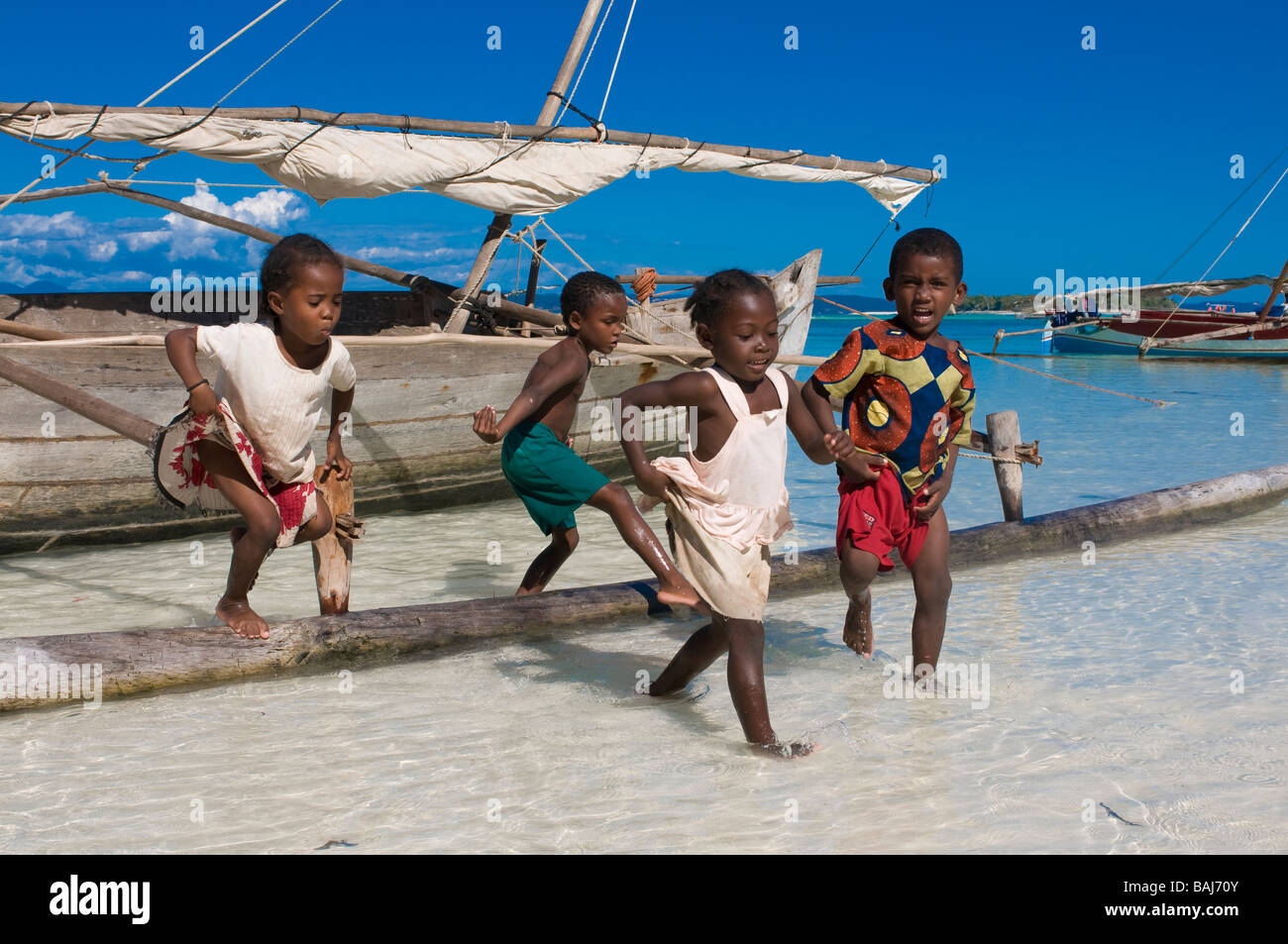Dark skinned children playing at wooden boat Nosy Iranja Madagascar Africa - Stock Image