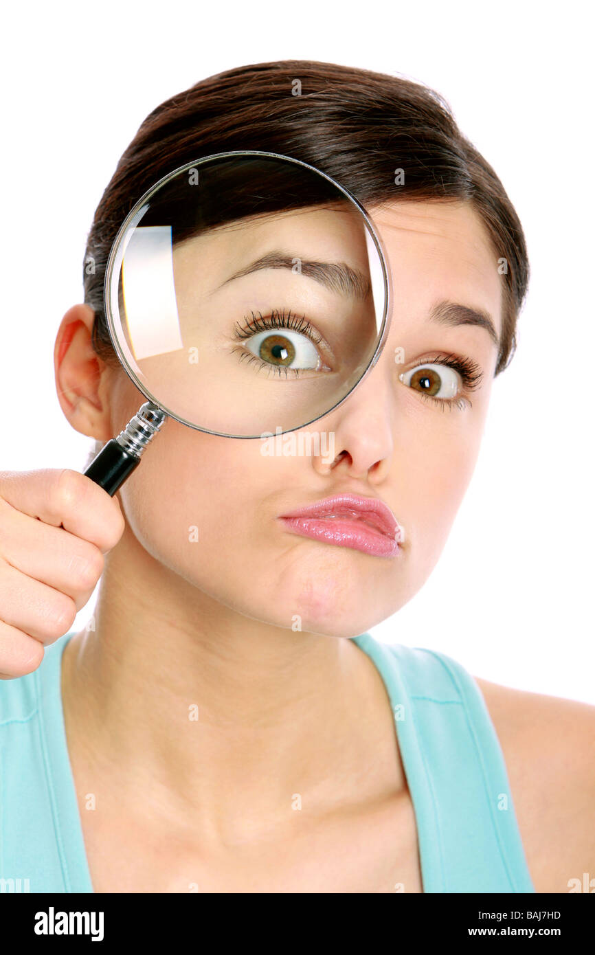 Junge Frau mit Vergroesserungsglas, eye of a woman oversized through a magnifier glass - Stock Image