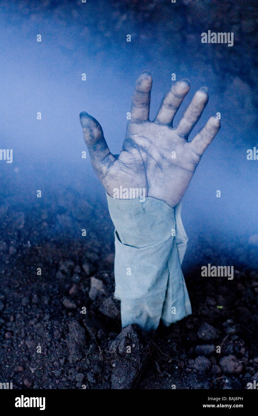 Zombie hand coming out of a fresh grave. - Stock Image