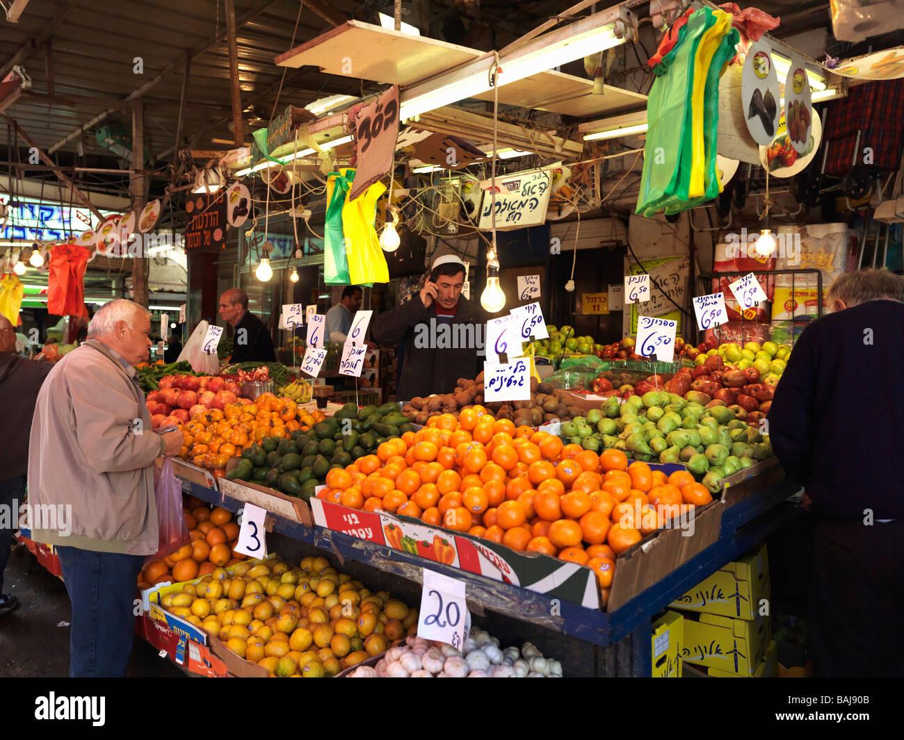 Israel Tel Aviv Carmel Market fresh fruit stand and shoppers Stock Photo