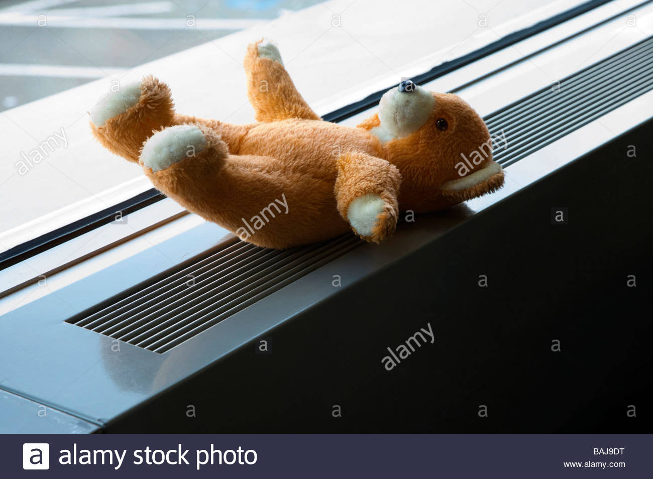 teddy bear left behind on a window sill inside - Stock Image