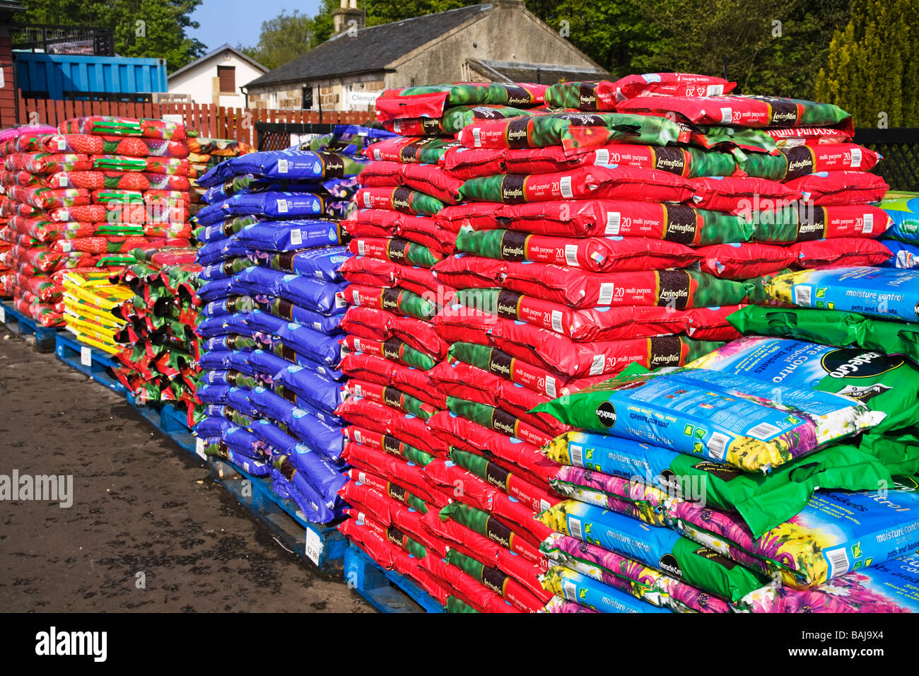 Bags of compost stacked on pallets at a garden centre. - Stock Image