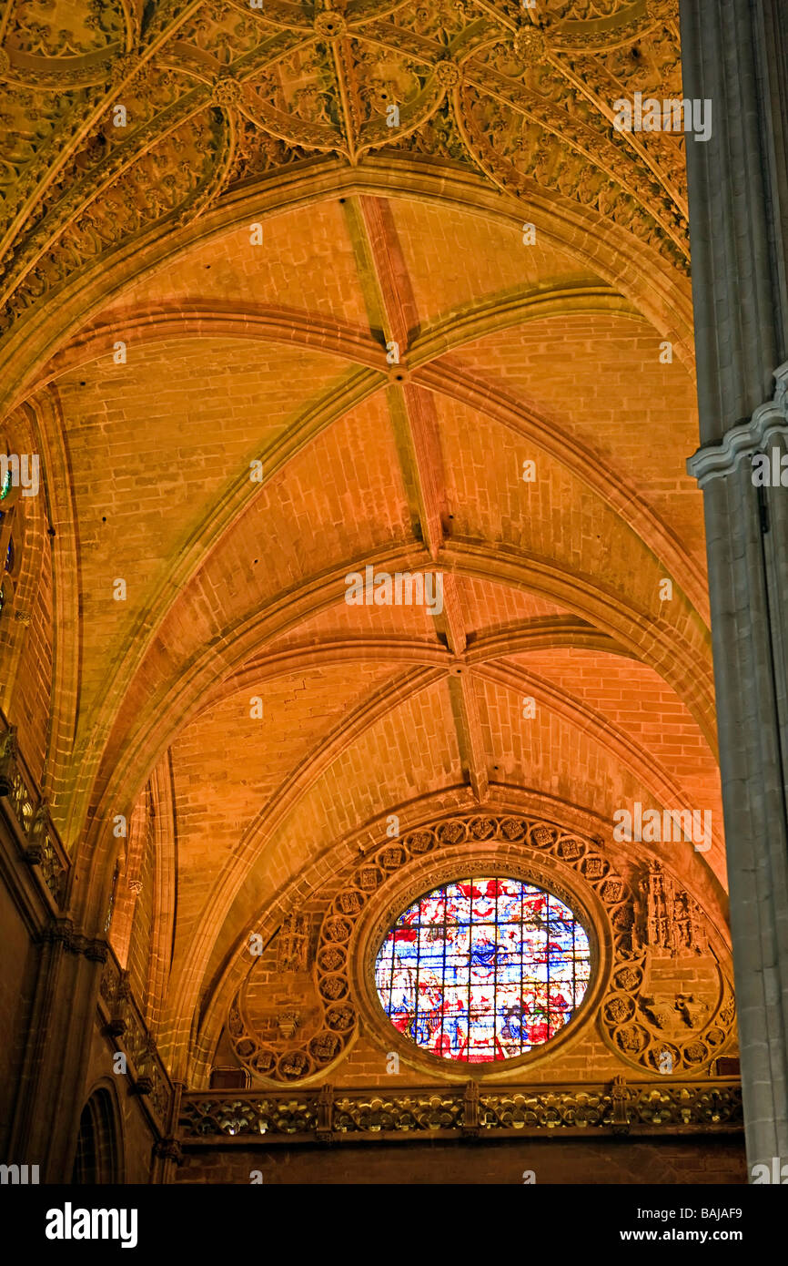 Stained Glass window and ceiling above the Door of the Prince (or of San Cristobal) at the Seville Cathedral and Stock Photo