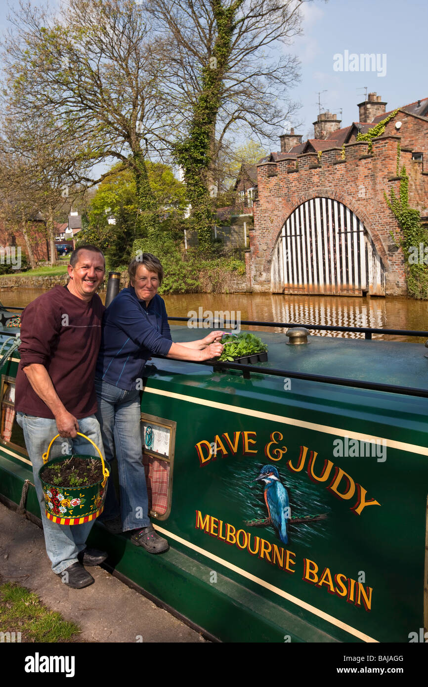 England Worsley narrowboat dwellers Dave and Judy Fridlington on the Bridgewater Canal dressing their boat with - Stock Image
