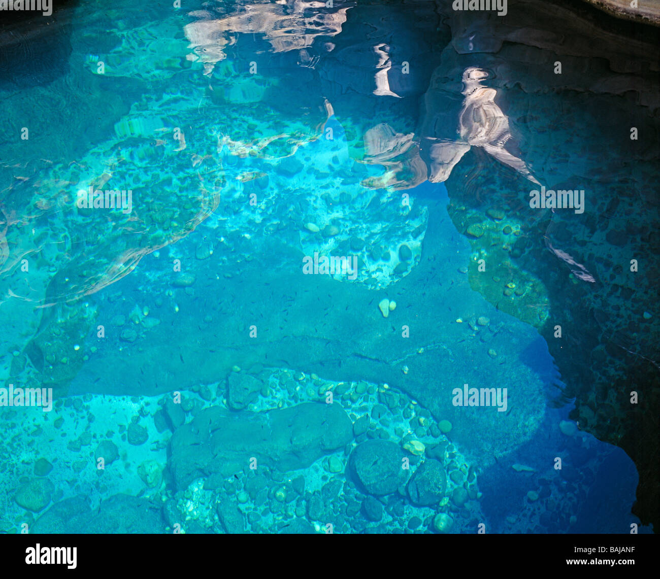 surreal reflections on the water surface of a turquoise coloured waterpool of Wadi Bani Khalid - Stock Image