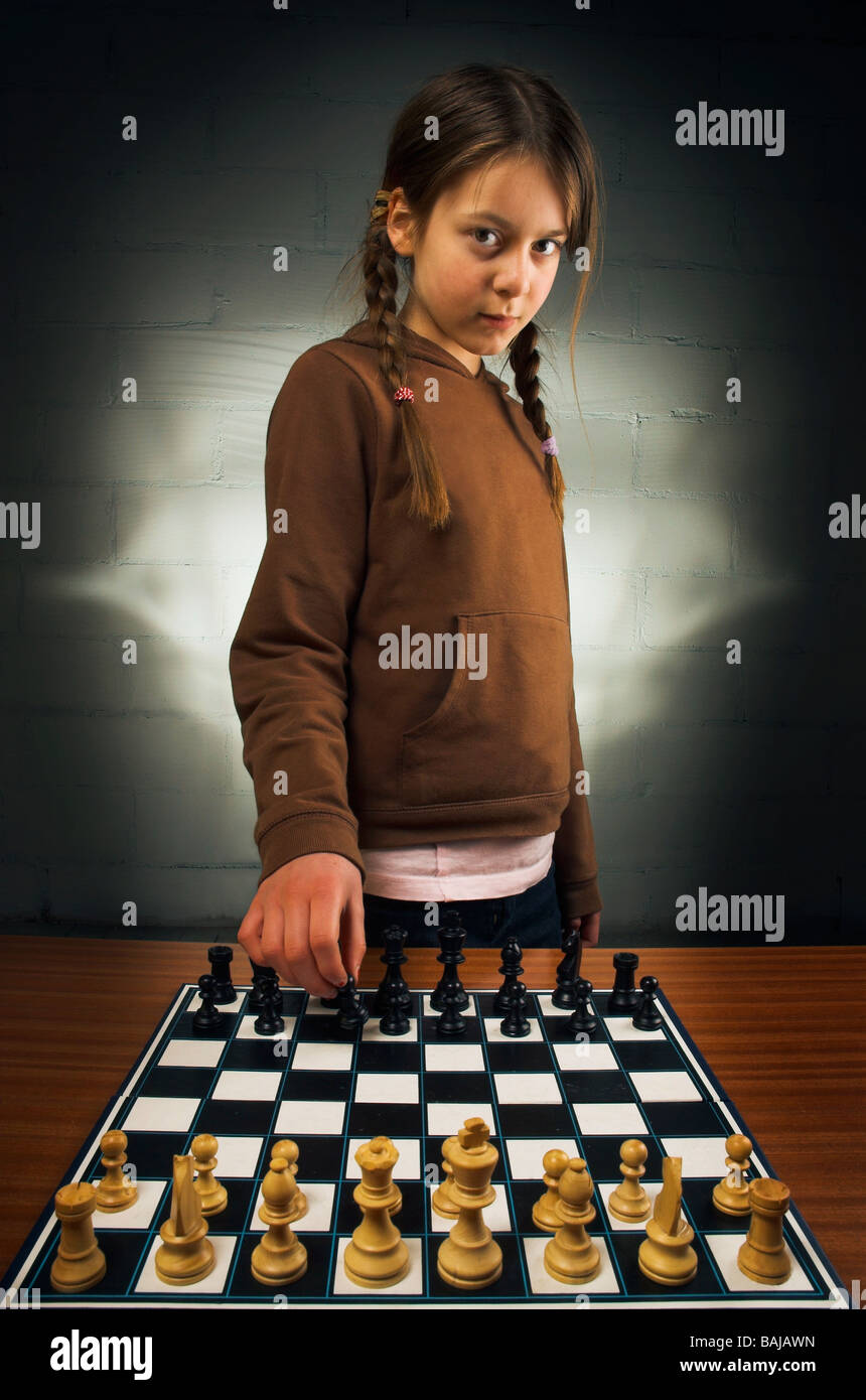 young girl (10) playing chess (breaking the rules and starting with black) - Stock Image