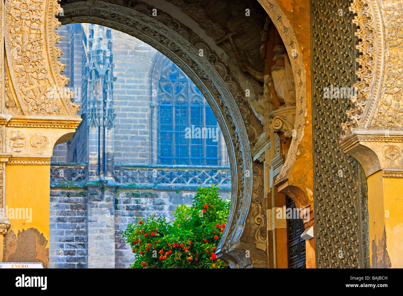 Looking through Puerta del Perdon (Door of Forgiveness),Seville Cathedral and La Giralda (bell tower/minaret). - Stock Image