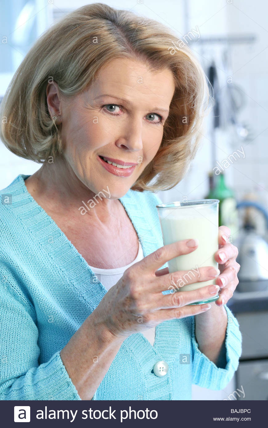 middle aged woman drinking a glass of milk standing in the kitchen Stock Photo