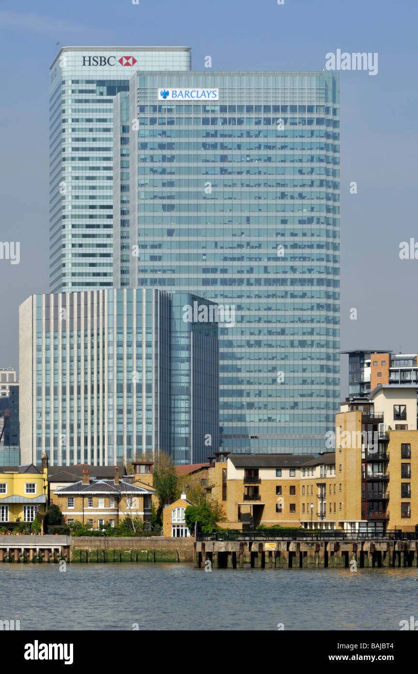 High rise offices and riverside apartments in the Canary Wharf development area in London Docklands beside River - Stock Image