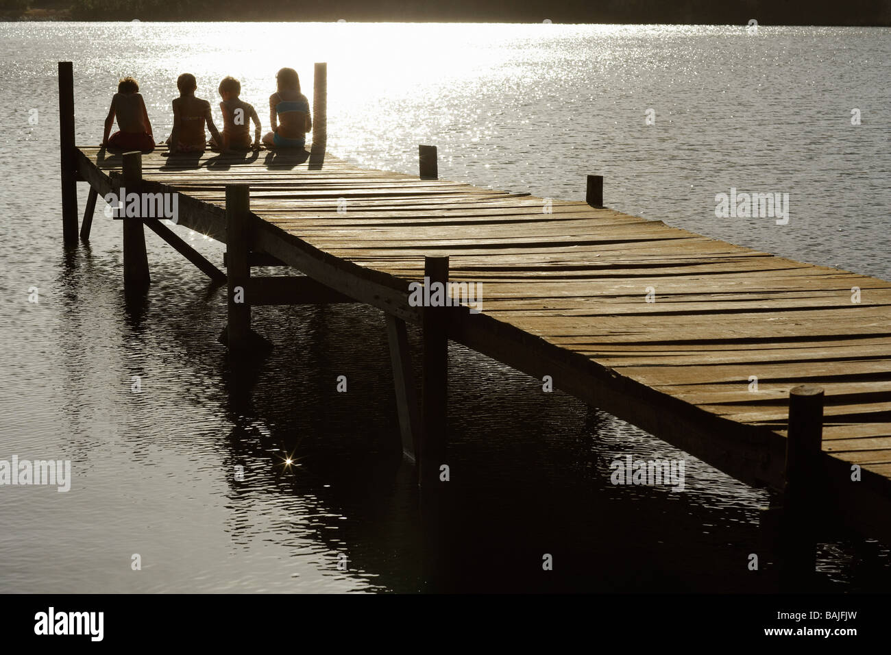 Four children (7-9) sitting on dock by lake, back view. Stock Photo