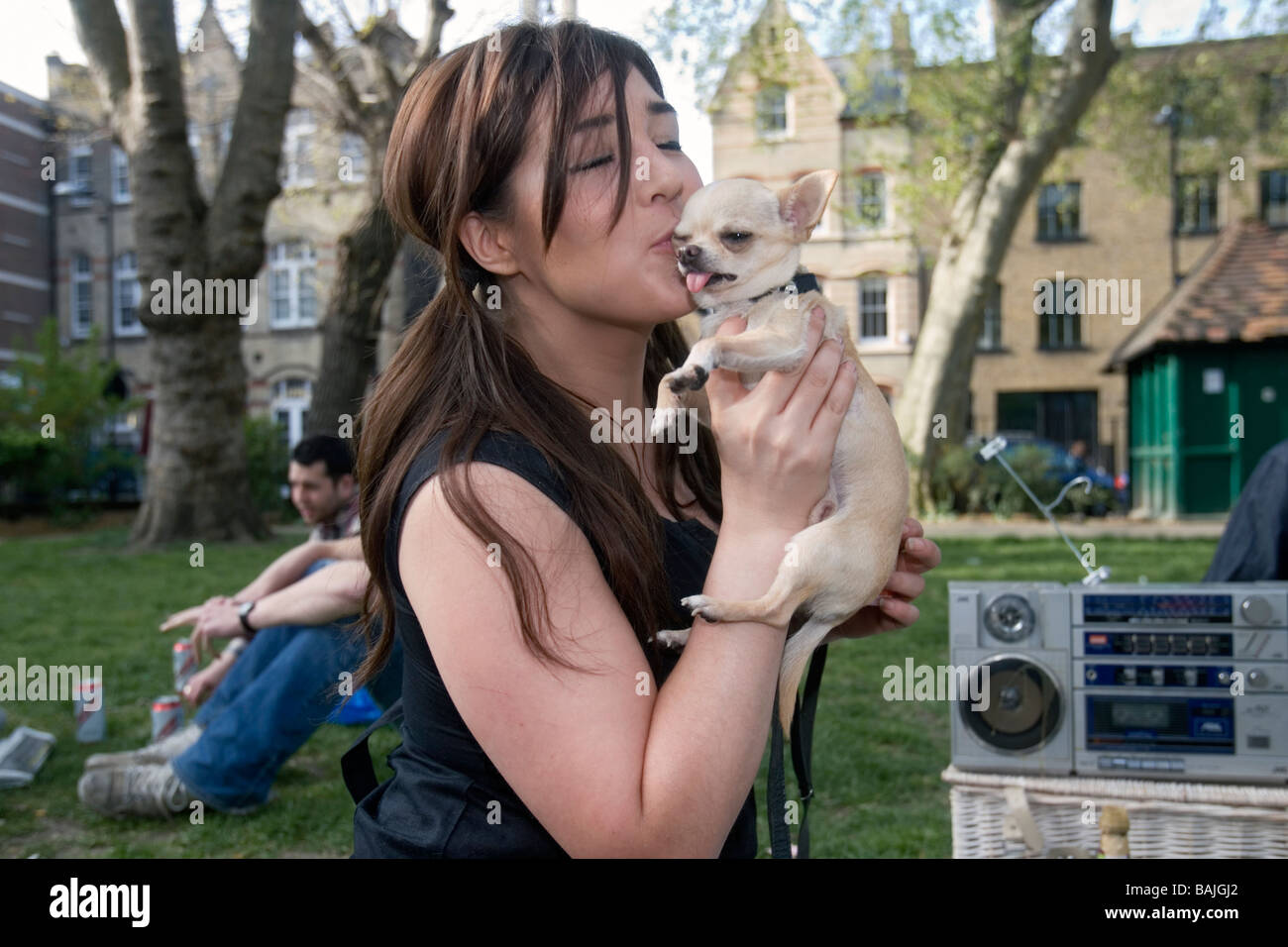 young woman with chihuaua in a london park - Stock Image