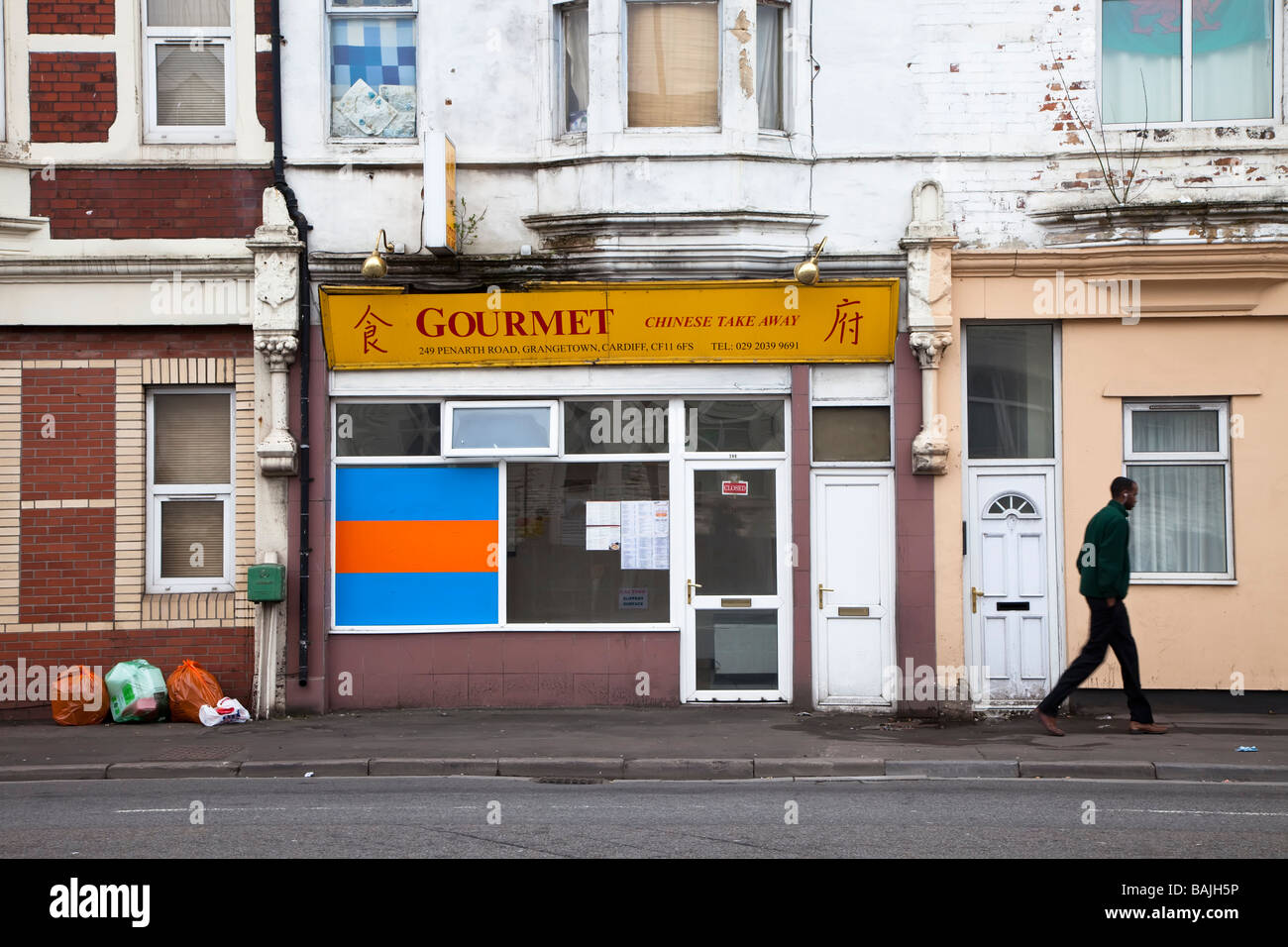 Man walking past Chinese take away shop in run down area of Cardiff Wales UK - Stock Image