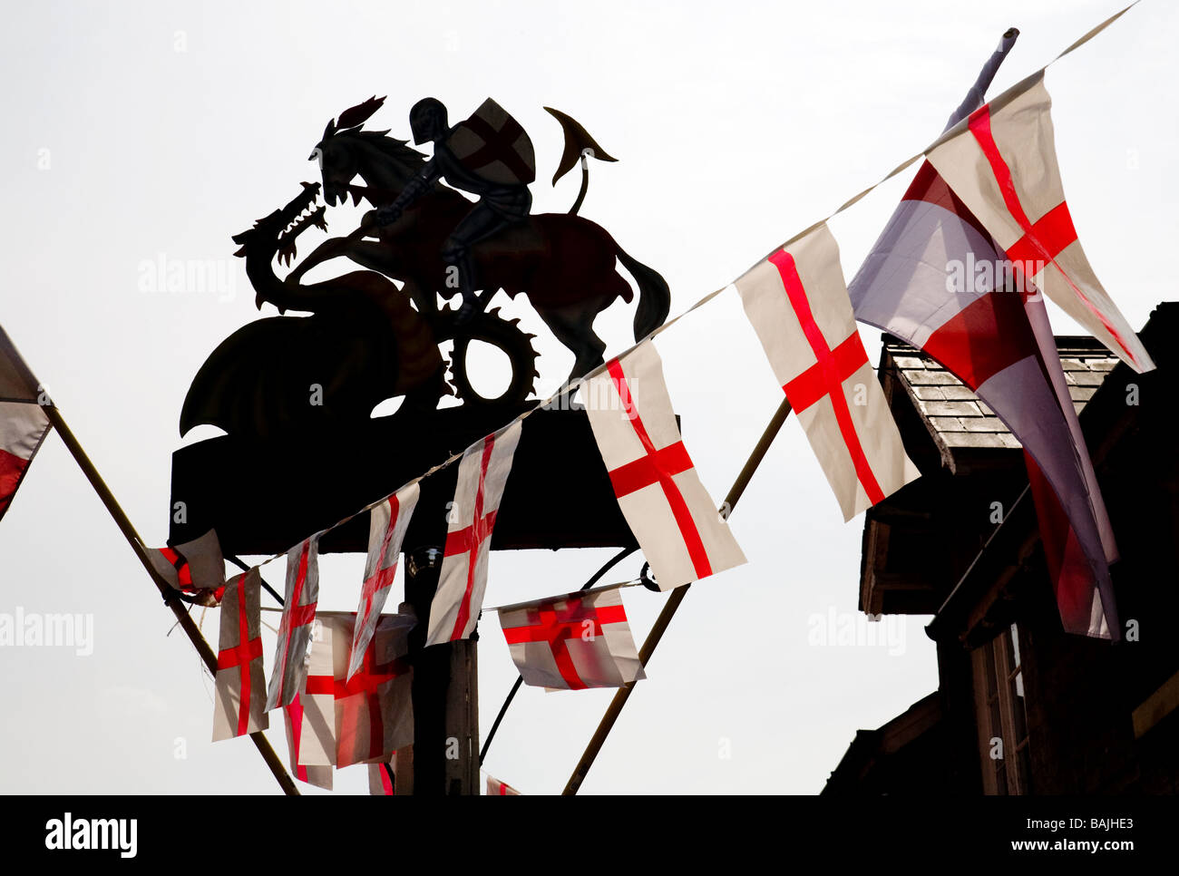 The George and Dragon pub sign, and flags of St George on St Georges Day, Snailwell, Cambridgeshire, UK - Stock Image