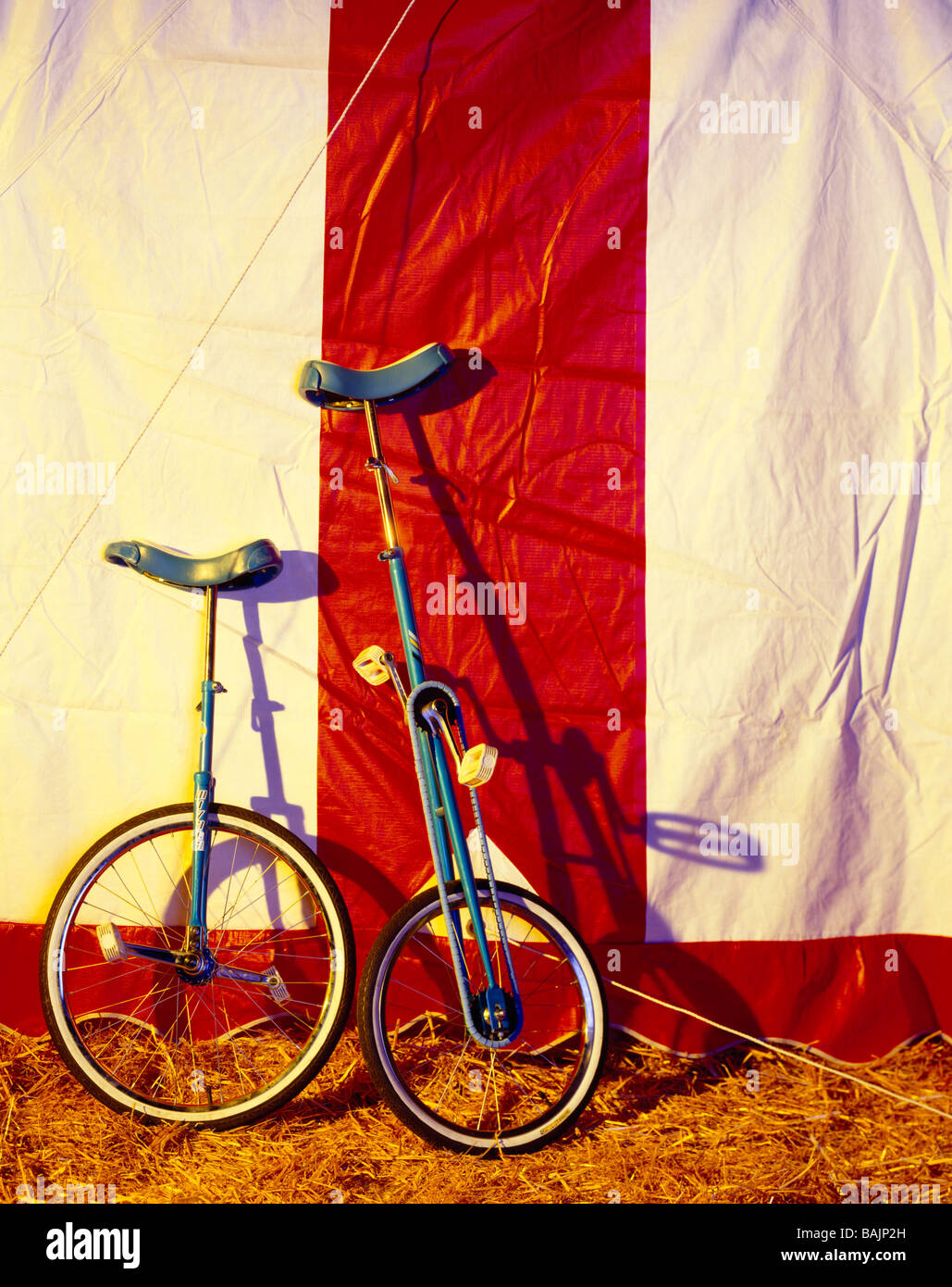 Circus unicycles resting against the big top tent - Stock Image