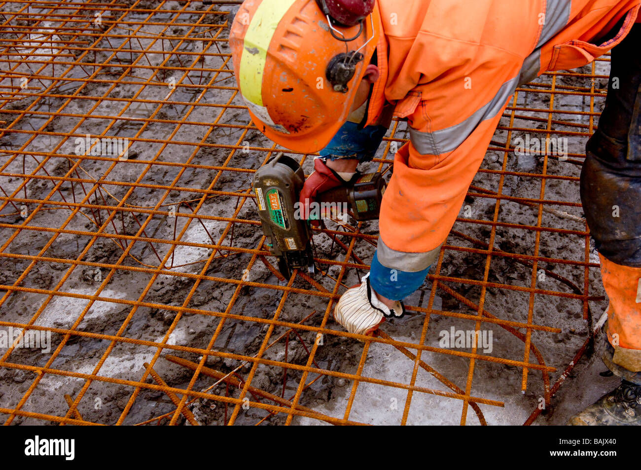 Construction workers putting reinforcement rods together before pouring concrete into the forms - Stock Image