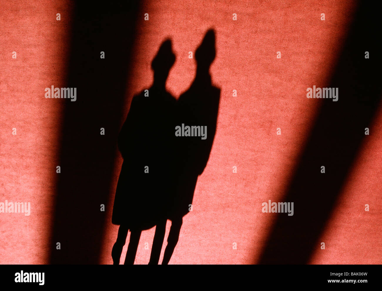 Abstract view of a couple s shadow cast on a red rug - Stock Image
