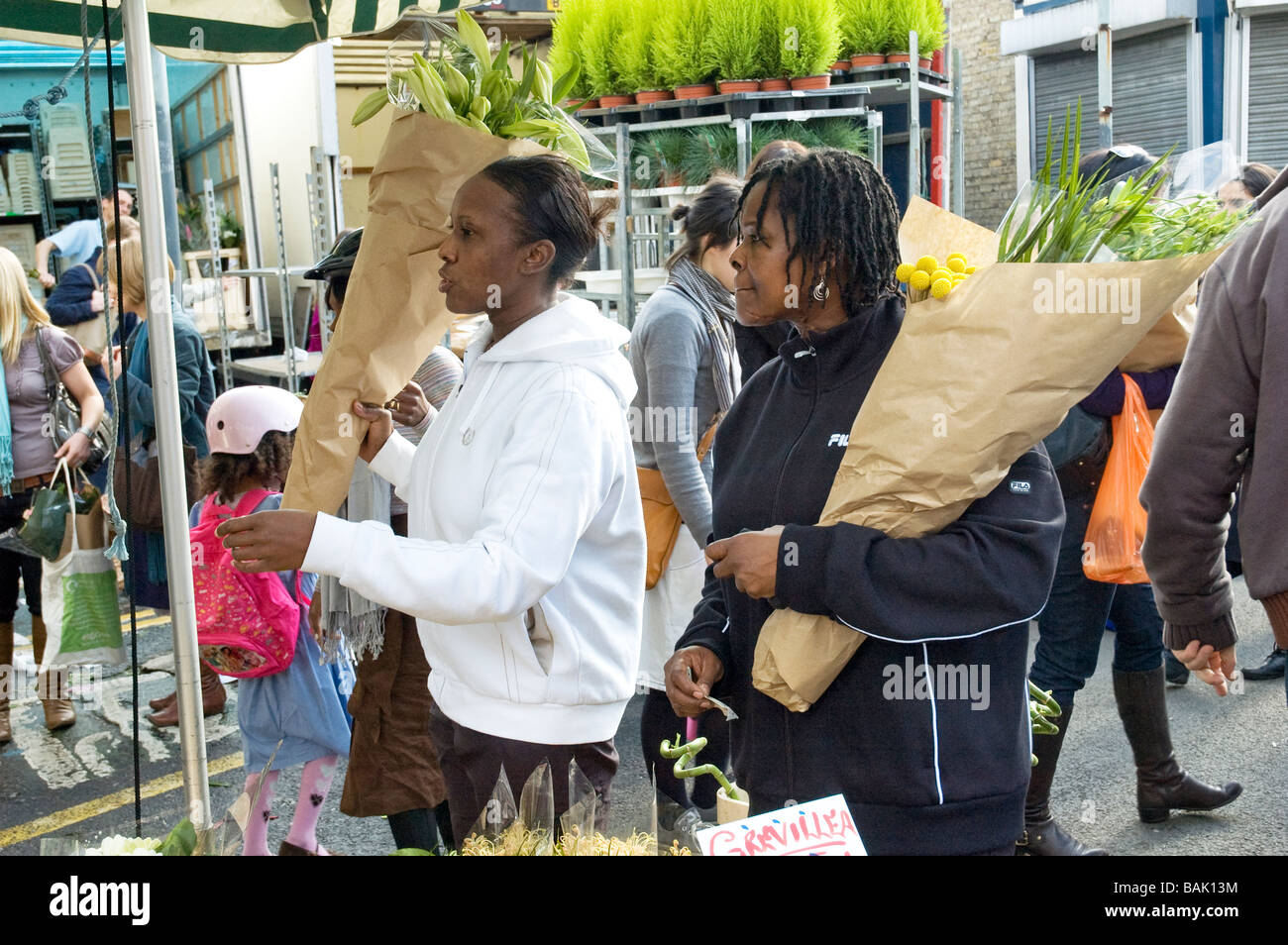 Two young women buying flowers in Columbia Road Sunday flower market Stock Photo