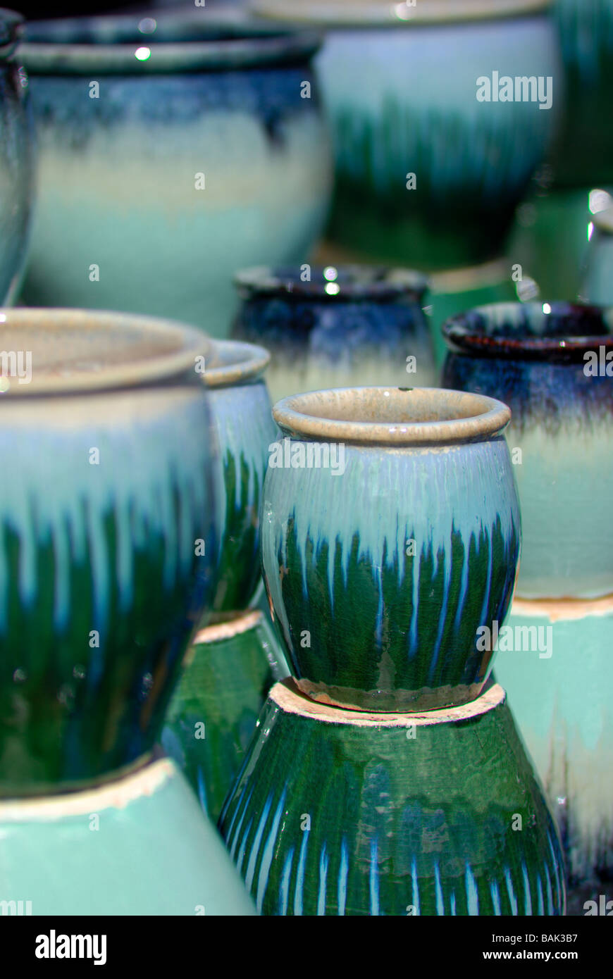 Green and aquamarine colored pottery at a garden center. - Stock Image
