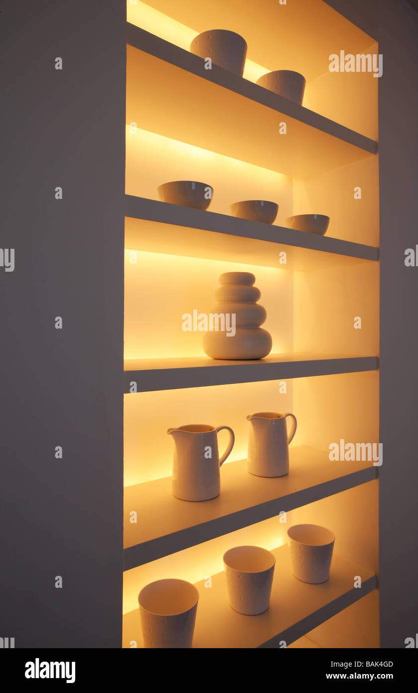 Clever lighting of a recessed shelving area in a white room - Stock Image