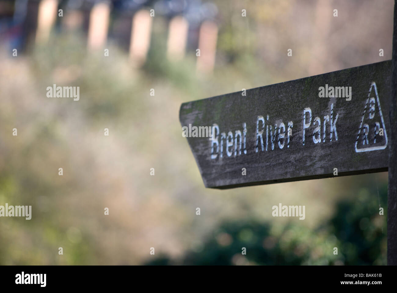 weathered left pointing wooden sign for a walking route to brent river park, west london, england - Stock Image