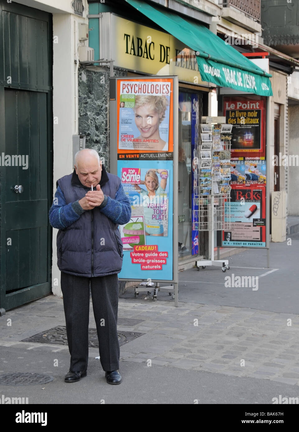 Man lightening his cigarette in front of a tobacco shop in Fontainebleau France - Stock Image