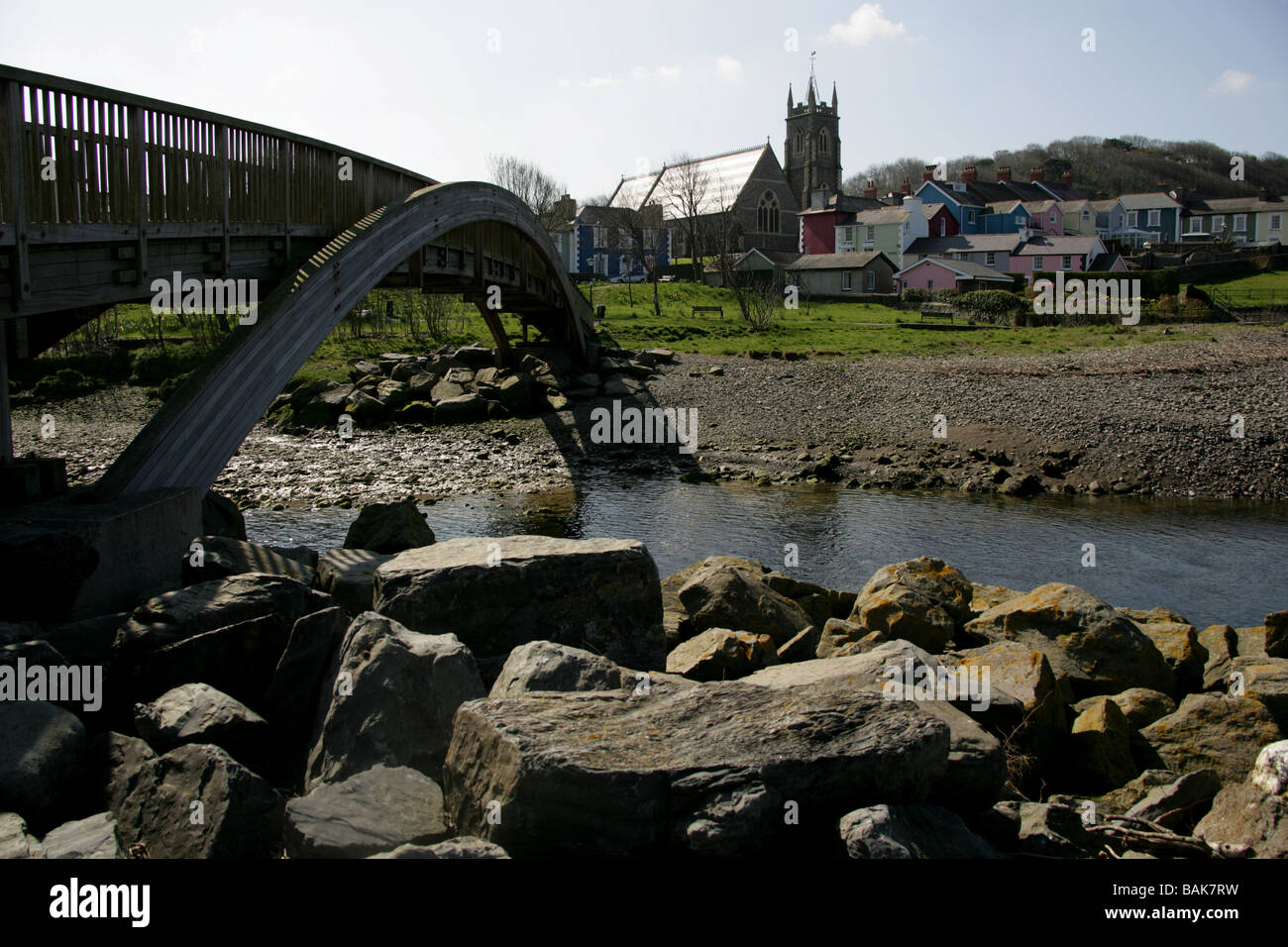 Town of Aberaeron, Wales. Wooden bridge over the River Aeron with the Holy Trinity Church at Bridge Street in the - Stock Image