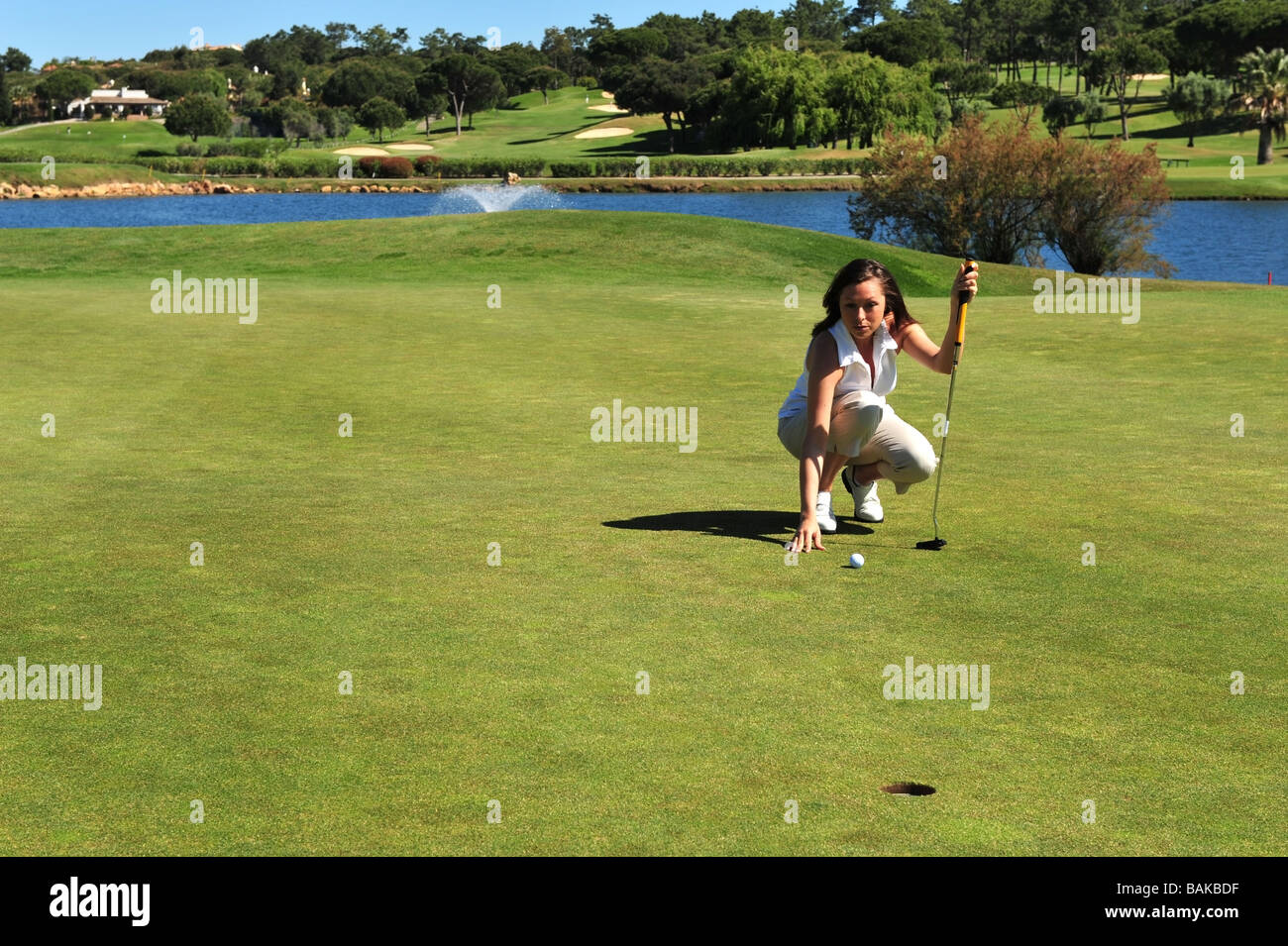 Lady golfer deciding on the best approach before taking her shot. - Stock Image