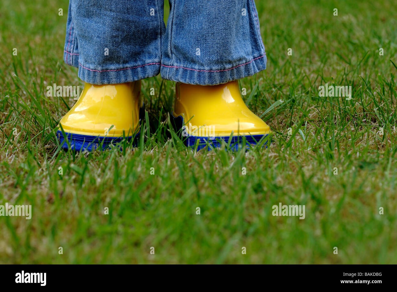 Girl on lawn wearing wellington boots - Stock Image