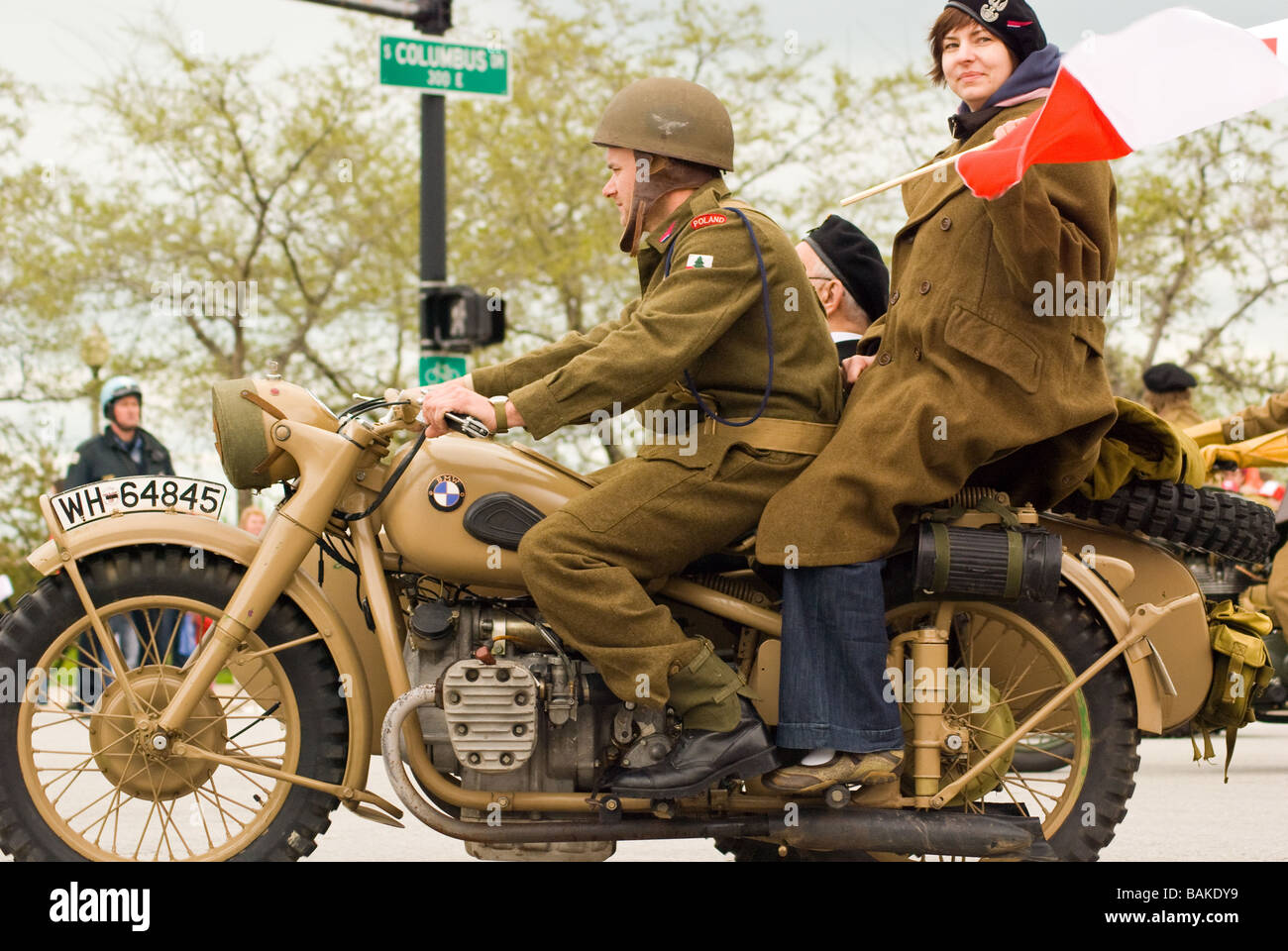 Man and woman in vintage Polish army uniform clothing riding antique motorcycle in Chicago Polish Parade Stock Photo