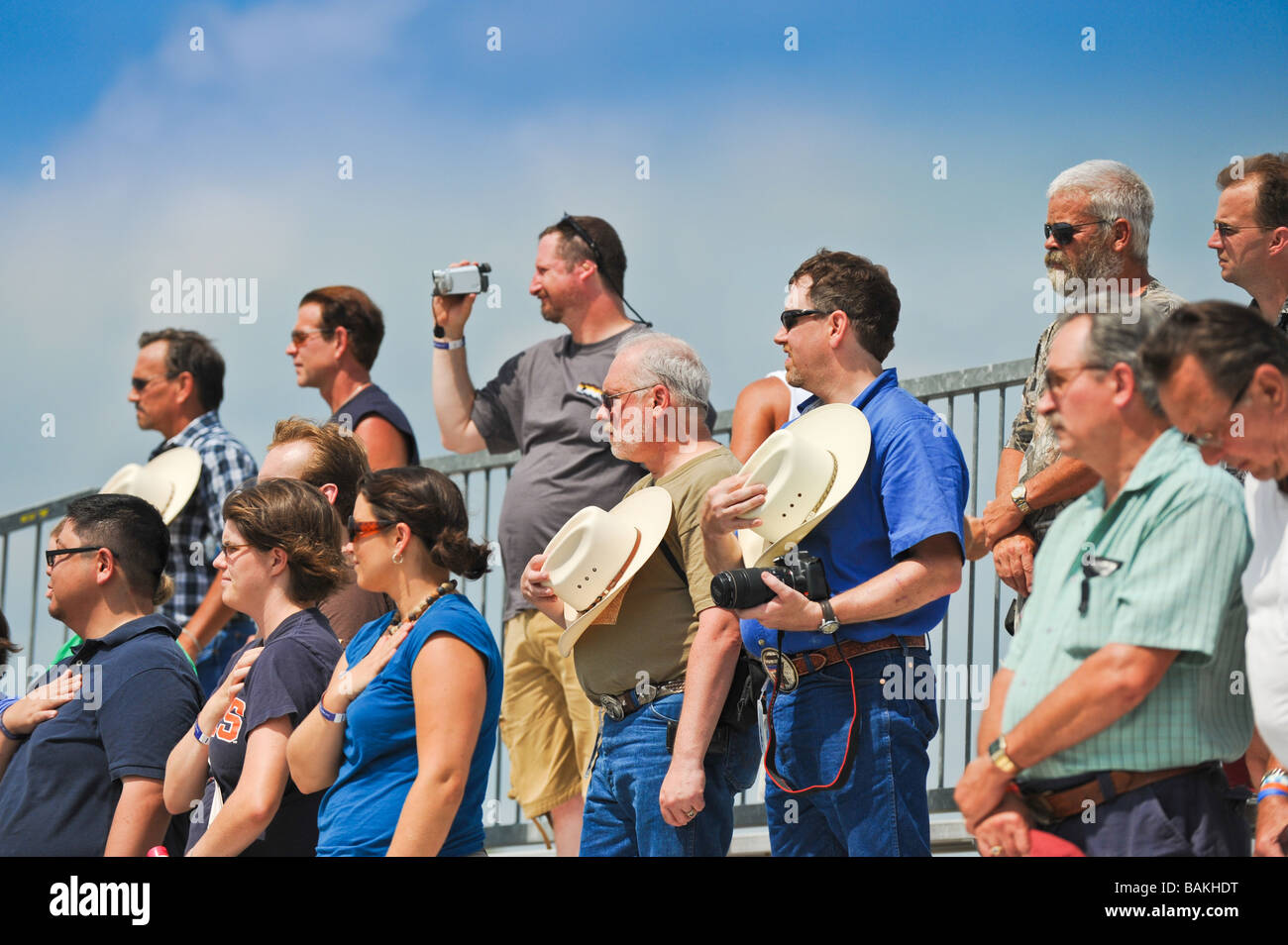 Audience in bleachers stand with hands and hats over hearts during national anthem - Stock Image