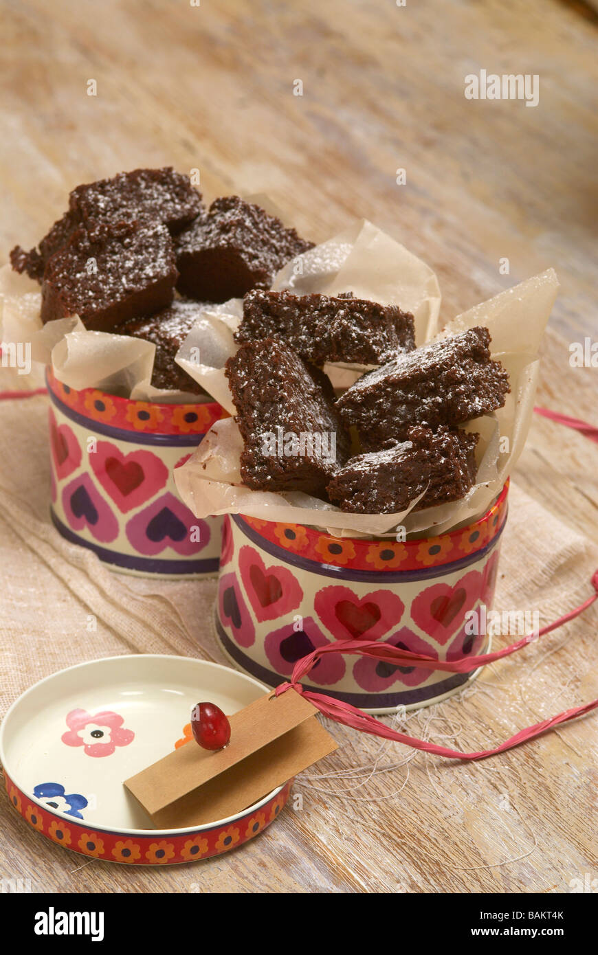 Chocolate brownies in tins surrounded by greaseproof paper - Stock Image