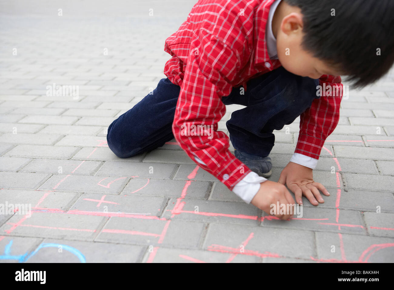 Boy Drawing On Sidewalk With Chalk - Stock Image