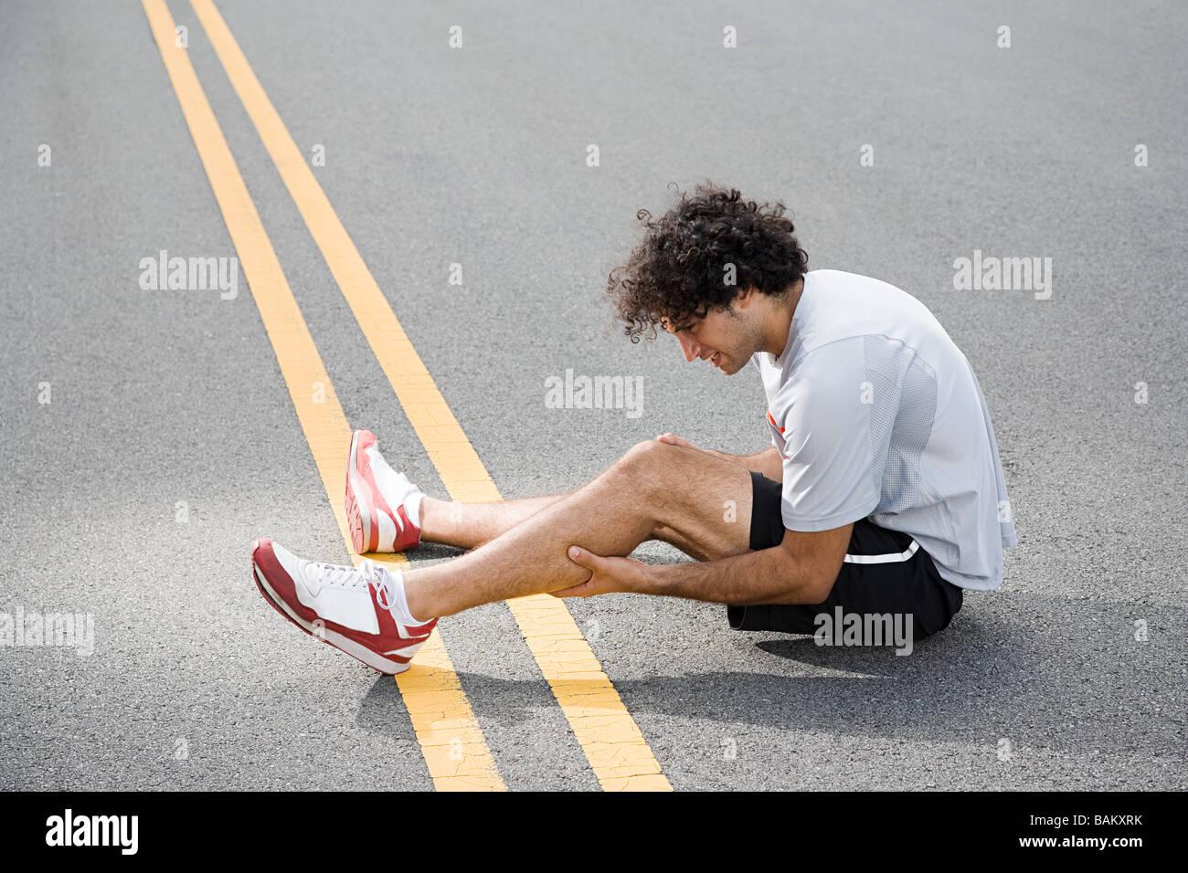 Runner with injured leg - Stock Image