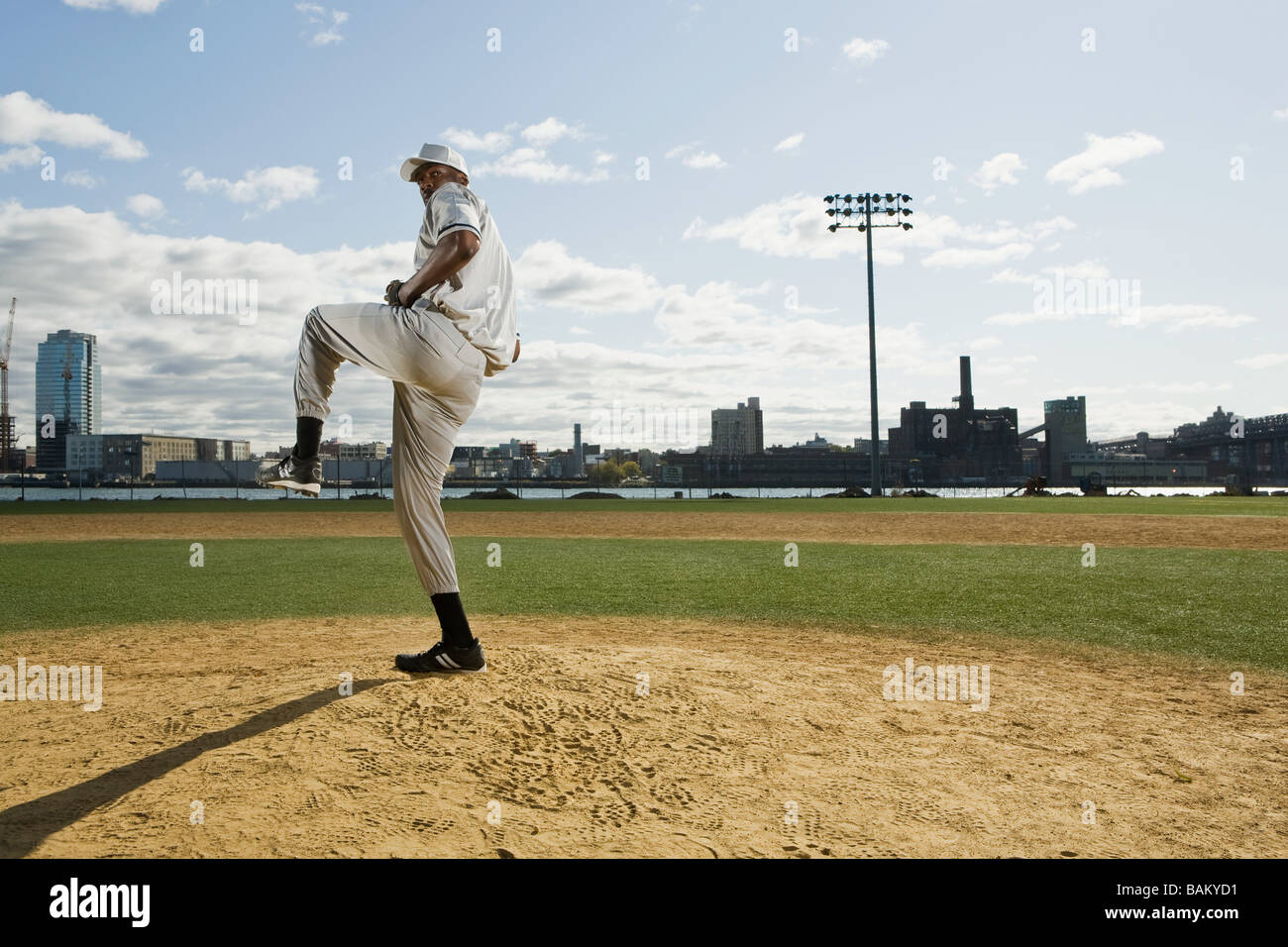 Baseball pitcher standing on one leg - Stock Image