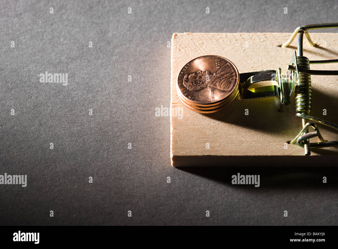 Coins on mousetrap Stock Photo