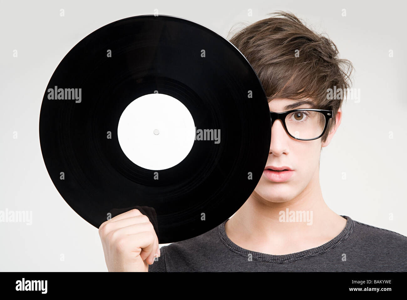 A teenage boy holding a vinyl record - Stock Image