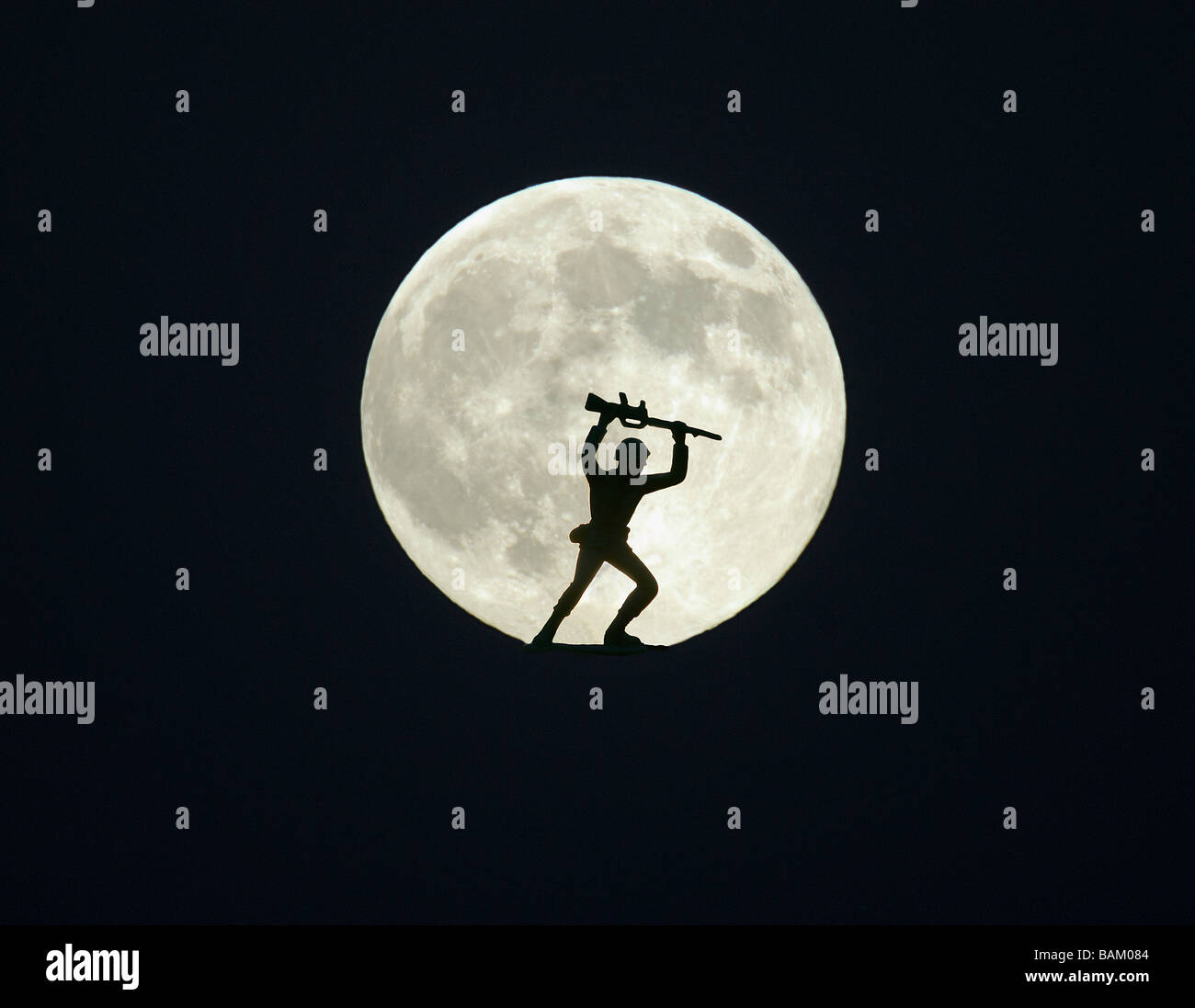 Toy soldier against full moon - Stock Image