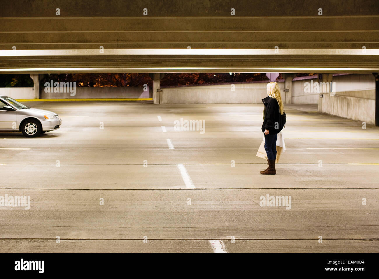 Woman in alone in parking lot - Stock Image