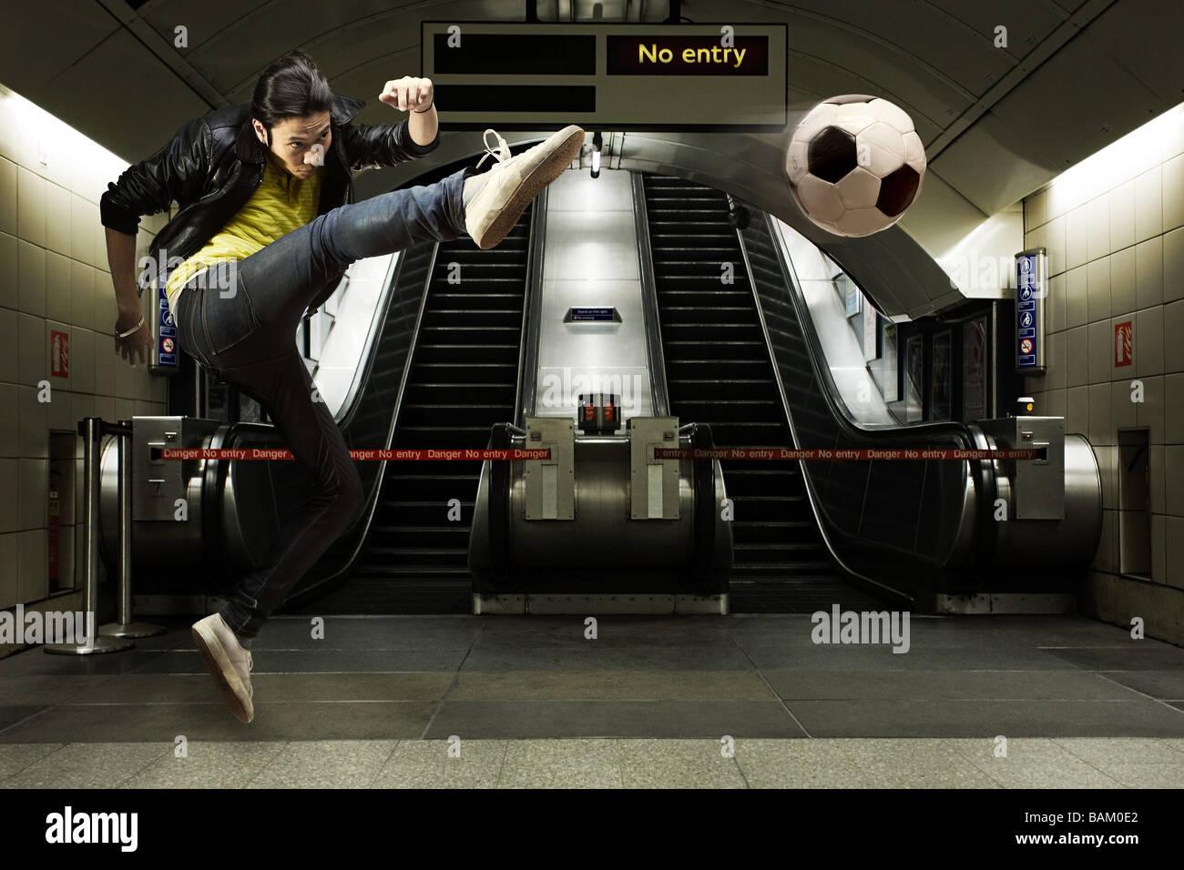 A young man kicking a football - Stock Image