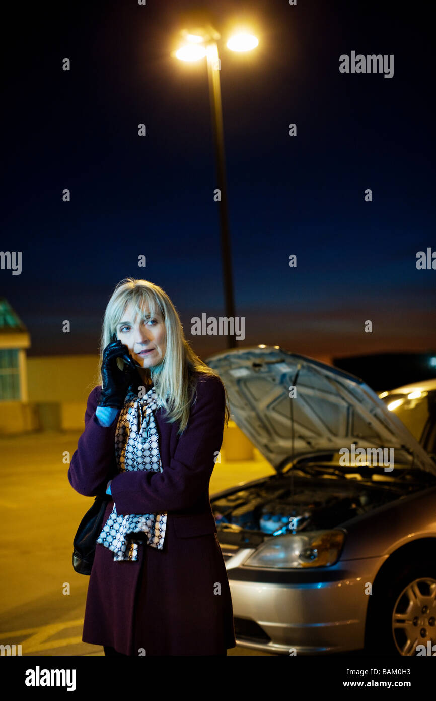Woman on cellphone with broken down car - Stock Image