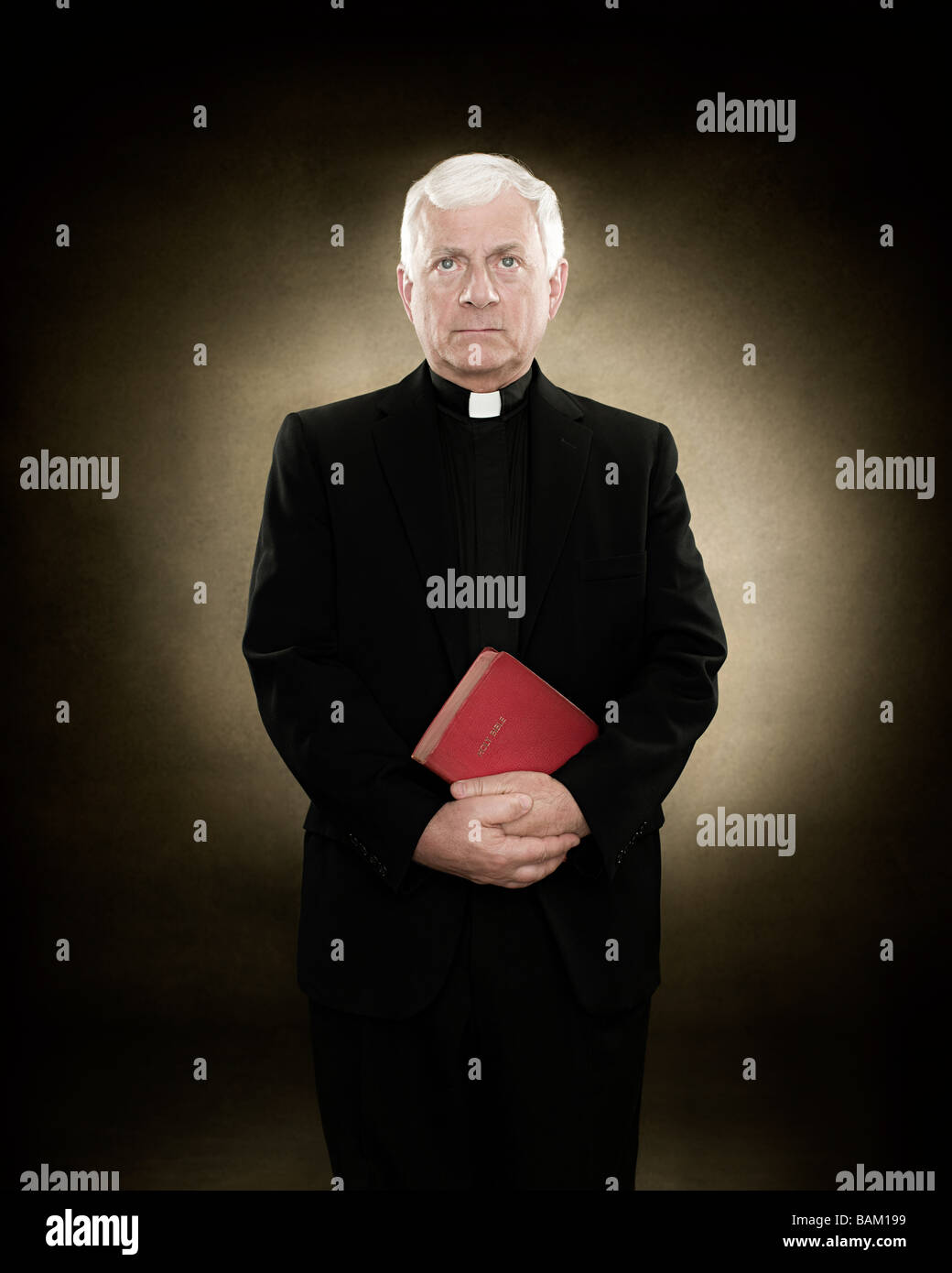 Portrait of a priest holding a bible - Stock Image