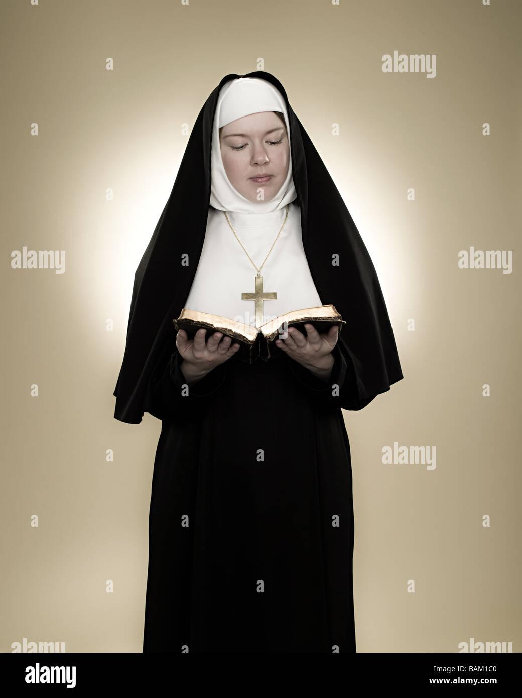 A nun reading a bible - Stock Image