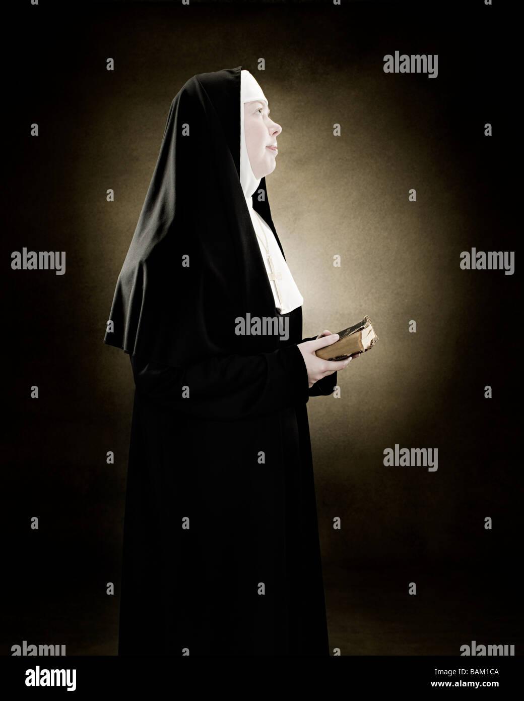 Profile of a nun praying - Stock Image