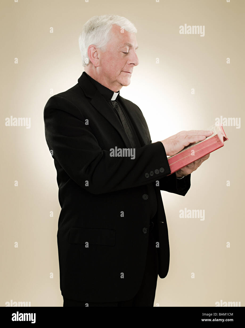 A priest reading a bible - Stock Image