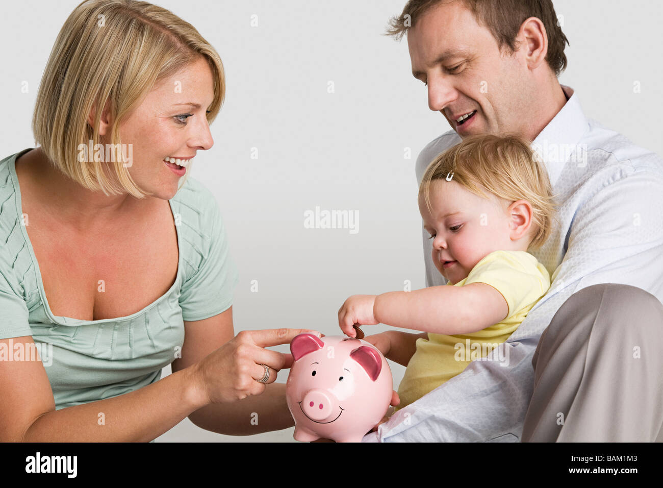 Parents and baby with piggy bank Stock Photo