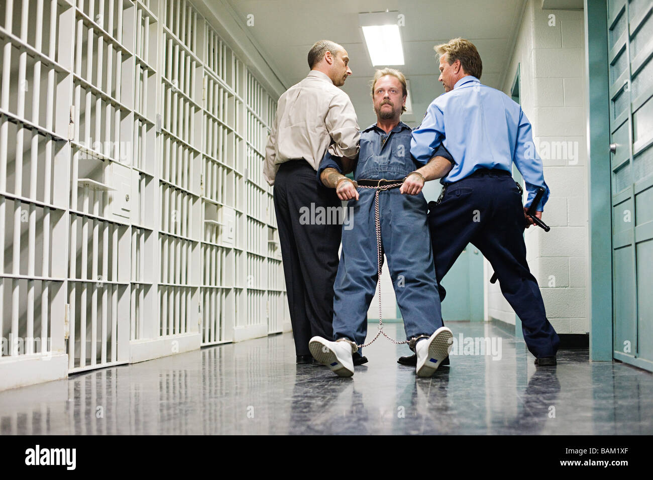 Prisoner being dragged down corridor - Stock Image