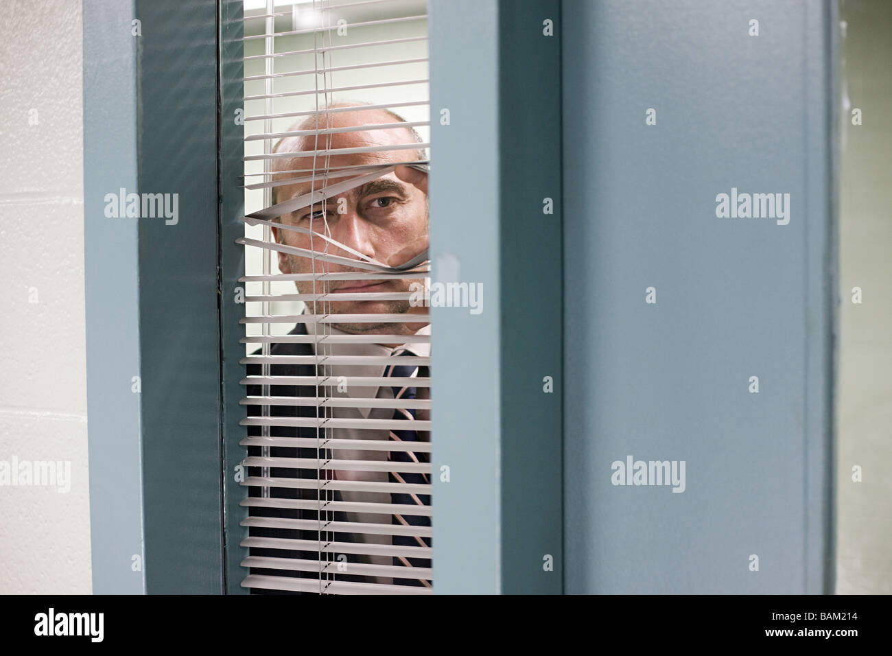 Detective looking through blinds - Stock Image