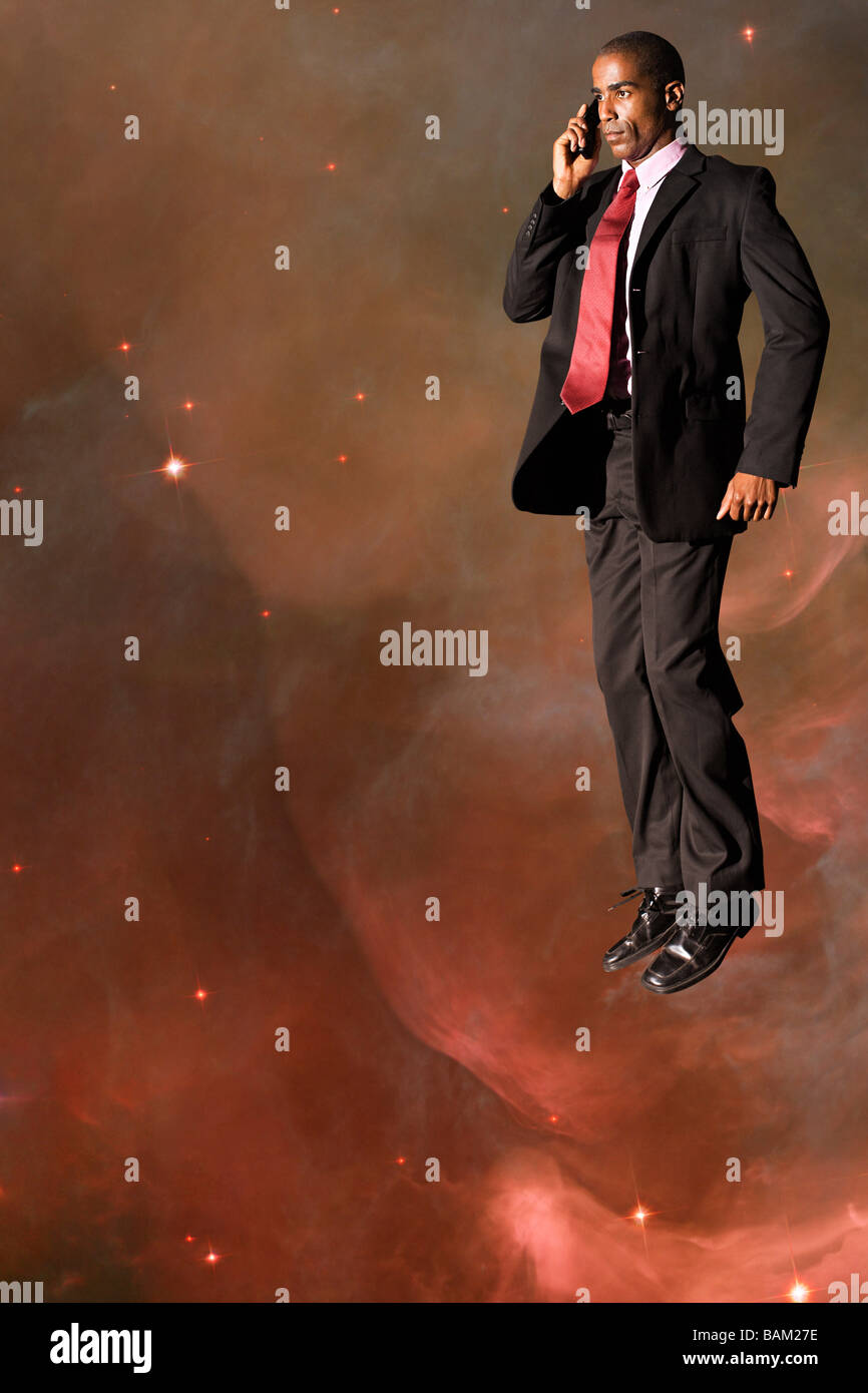 Businessman on cellphone in outer space - Stock Image